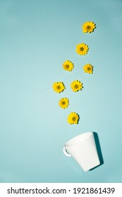 flat lay white cup on a blue background with small flowers