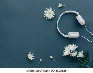 Flat Lay White Headphones and spring flowers over blue background