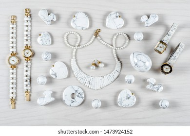 Flat lay white howlite items on white wooden background. Top view semi precious jewelry concept.