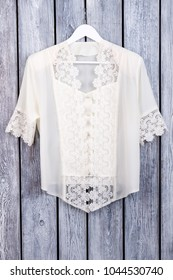 Flat lay white lace blouse. Top view, flat lay. Dark wooden surface background.