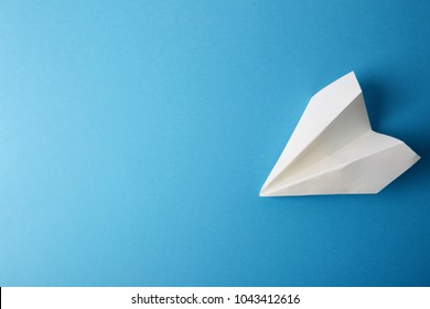 Flat lay of white paper plane and blank paper on pastel blue color background.Horizontal