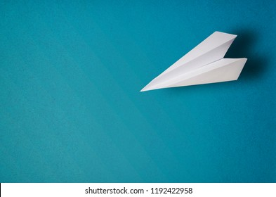 Flat lay of white paper plane and blue background. Travel concept mock up.
