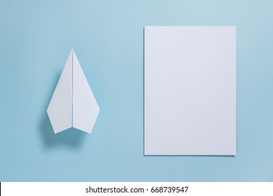 Flat lay of white paper plane and blank paper on pastel blue color background