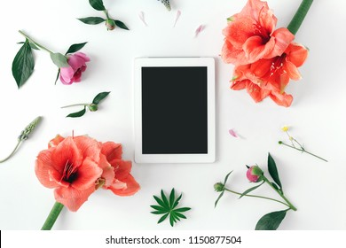Flat lay white tablet with blank desktop screen and flowers peonies, amaryllis on white background, top view