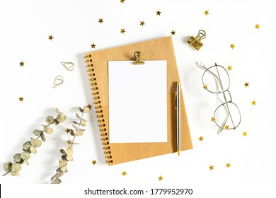 Flat lay of white working table background with office equipment putting on it. Top view craft Notebook, eucalyptus, golden paper binder clips, blank greeting card and pen. Desktop mock up scene.