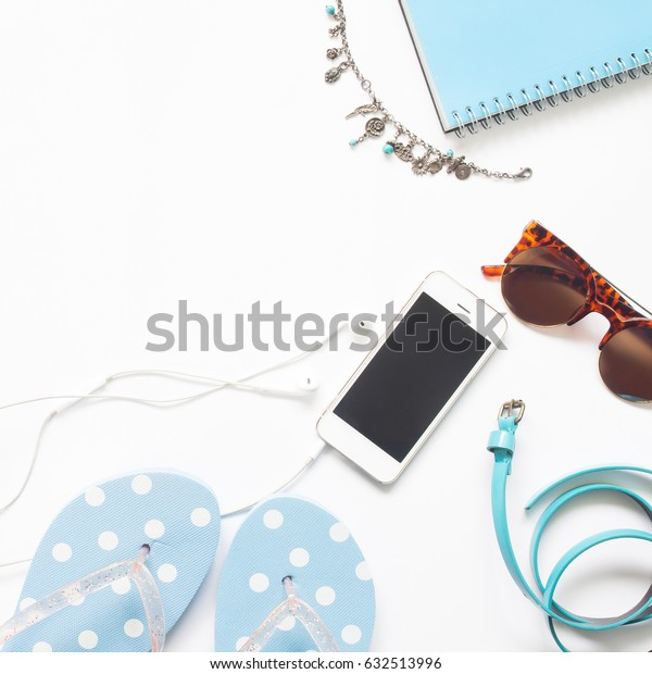 Flat lay of woman accessories in blue color collection with smart phone isolated on white background