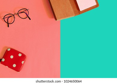 Flat lay of woman fashion accessories of purse, eyeglasses, notebook with two tone color of orange and green