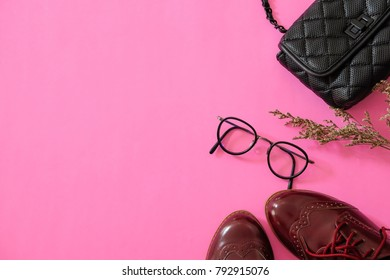 Flat lay of woman fashion accessories with shoe, handbag; eye glasses and dry flower on pink background with copy space for valentine theme