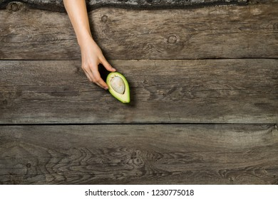 Flat lay with woman hand elegantly touching  half cut avocado on wooden background
