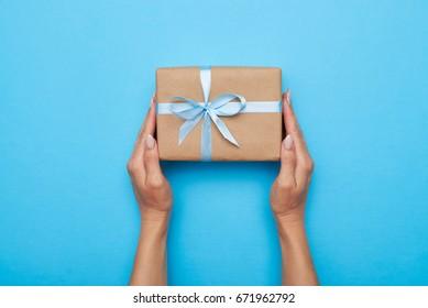 Litteä makasi naisen kädet tilalla lahja kääritty ja koristeltu keula sinisellä taustalla kopiotilaa