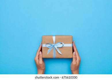 Flat lay of woman hands holding gift wrapped and decorated with bow on blue background with copy space