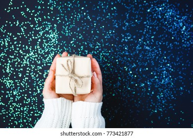 Flat lay of woman hands holding gift wrapped and decorated with bow on dark background with stars and copy space