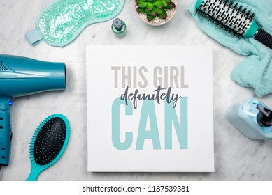 "Flat lay of women's beauty products with inspirational quote that says ""This girl definitely can"" - empowerment concept"