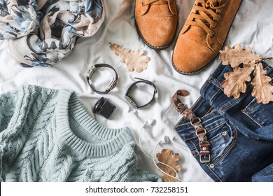 Flat lay women's clothing for autumn walks, top view. Brown suede boots, jeans, a blue pullover, scarf, bracelets, watches, headphones, perfume on a light background. Fashion concept