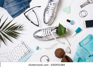 Flat lay women's items. Sneakers, blue shirt, watch and leaf of a palm tree on a white background
