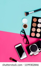 Flat lay womens travel accessories on colorful blue and pink background with cosmetics, smartphone, glasses and camera. Closeup, top view, copy space