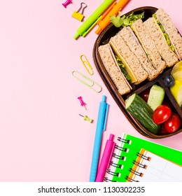 Flat lay with wooden lunch box with sandwiches, vegetables and fruits on pink background and school supplies. Healthy children eating concept. Top view with copy space.