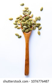 Flat lay of wooden spoon filled with pumpkin seeds lying on white backgroun