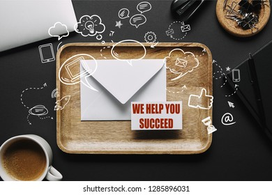 "flat lay with Wooden tray with envelope and business card with ""we help you succeed"" lettering on black background with laptop and stationery"