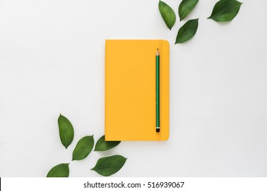 flat lay of workplace on white desk with yellow notebook and green leaves
