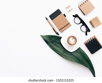 Flat lay Workplace table composition with coffee, stationery, green leaf on white background