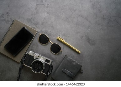 Flat lay of workspace desk of male gadget and accessories, smartphone, sunglasses, wallet, camera and notebook on dark stone background, top view with copy space, business and lifestyle concept