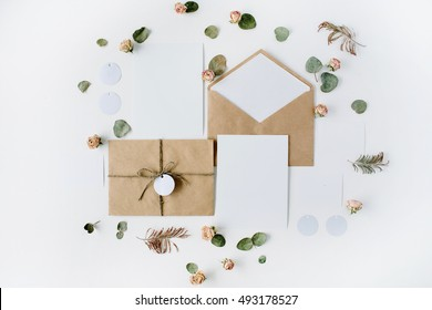 Flat lay workspace. Wedding invitation cards, craft envelopes, pink and red roses and green leaves on white background. Overhead view, top view