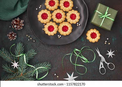 Flat lay with Xmas decorations in gray and red and jam cookies ready for wrapping in gift boxes on dark background