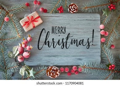 """Flat lay with Xmas decorations in green and red with frosted berries, trinkets and Christmas tree twigs, text """"Merry Christmas"""""""