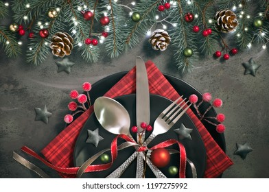 Flat lay with Xmas decorations in green and red with frosted berries, trinkets, plates and crockery, Christmas menu concept