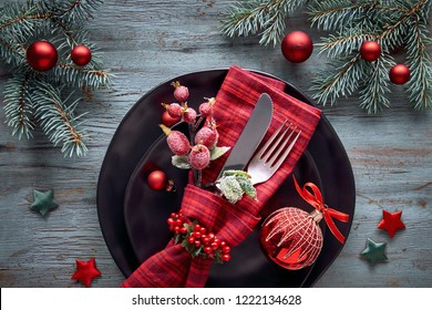 Flat lay with Xmas decorations in green, blue and red with frosted berries, trinkets, plates and crockery, Christmas menu concept