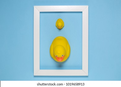 Flat lay of yellow ducks in white wooden frame on blue background minimal concept