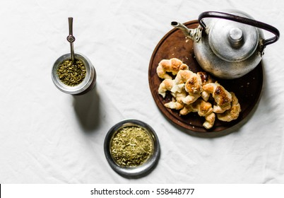 Flat lay of yerba mate tea, croissants on a wooden board, and kettle against white background. Focus on the calabash gourd.