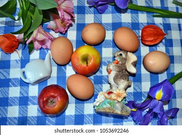 Flat layout of Easter eggs, iris flowers, Peruvian lilies, cape gooseberries, teapot, apples and Easter bunny on the blue-white checked tablecloth, Easter decoration