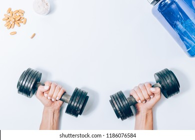 Flat layout female hands holding metal dumbbells next to protein powder and vitamin pills, top view. Concept of improving body strength using heavy weights equipment and sport nutrition additives.