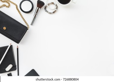 Flat Layout of Feminine Items in Black and Gold Tones with Purse, Makeup, Coffee, and Notebook, on White Background with Room for Copy