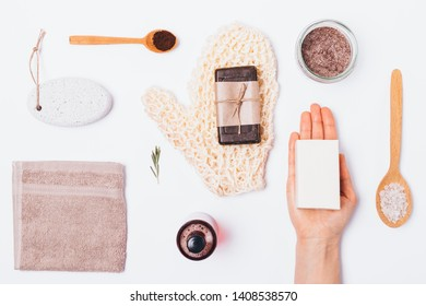Flat layout of organic bath accessories and beauty products for cleansing and exfoliating body skin. Top view massage washcloth, coffee scrub and soap on white background, knolling style.