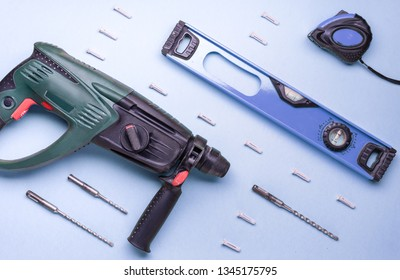 Flat layout: perforator and other hand tools for construction and repair on a blue background.