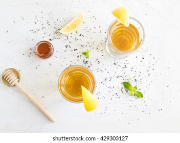 Flat layout of two tea cups, honey, lemon and mint on white scratched background