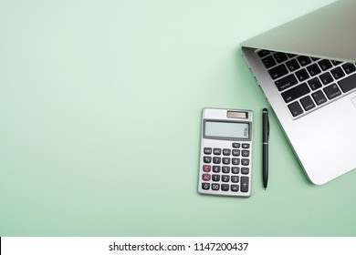 Flat lay,Top view office table desk. Workspace with calculator, black pen , laptop on the indigo Green background.Copy Space for text,Empty Blank to word.Business Finance,Education Technology Concept.