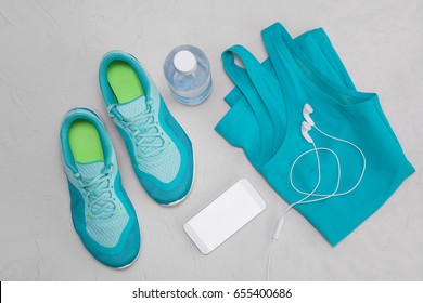 Flat light blue athletic shoes, a bottle of water, a T-shirt and headphones on a gray concrete background. The concept of a healthy lifestyle, sport and diet. Sport equipment. view from above.