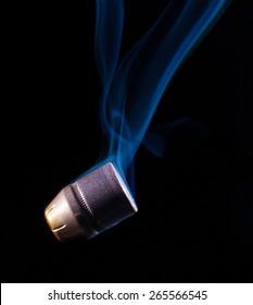 Flat nosed handgun bullet with blue smoke behind