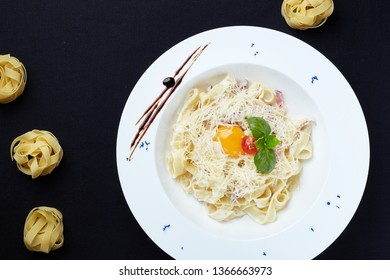 Flat overhead shot of pasta carbonara with fettuccine, liquid egg yolk, cherry tomato, basilic, and grated parmigiano cheese. Sweet caramel sauce and dry pasta balls added as decoration