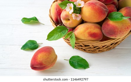 Flat peach with green leaves On a white wooden background.