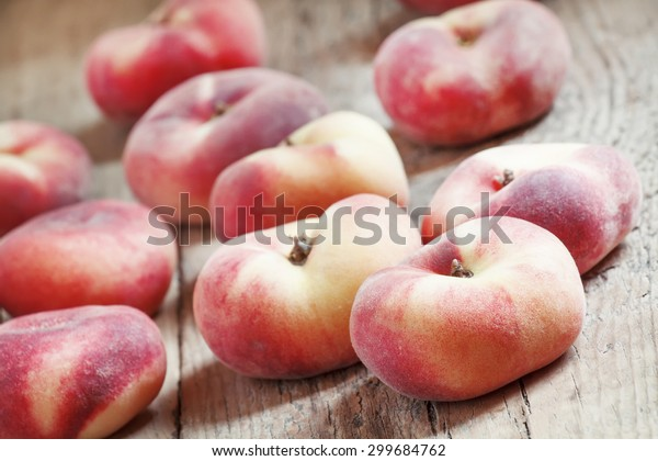Flat pink peach on an old wooden background, selective focus