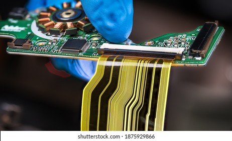 Flat plastic strip flexible cable on printed circuit board on a dark background. Hand in blue glove holding green PCB with integrated motor stator and electronic components as micro chip or resistors.