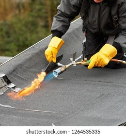 Flat roof covering with roofing felt melting bitumen with burner