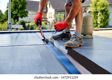 Flat roof installation with propane blowtorch during construction works with roofing felt. Heating and melting bitumen roofing felt. Roofing felt. Roofer working. Roofer working tool. Waterproofing