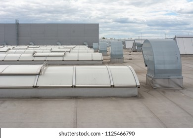 Flat roof with many large skylights and hydro insulation membranes on modern industrial hall or building