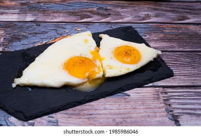 Flat shot of fried eggs in cutting board on wooden table